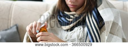 Close-up Of Ill Woman Opening Bottles With Medication. Sickness Female Person Wrapped Up In Blanket
