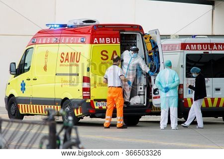 Health-care staff take out a patient with covid-19 symptoms from an ambulance in La Fe hospital during the state of alarm for the coronavirus crisis in Valencia, Spain on May 15, 2020.