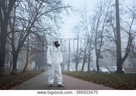 Full Length Of Male Environmentalist In Safety Respirator Standing On Sidewalk And Looking Aside. Re