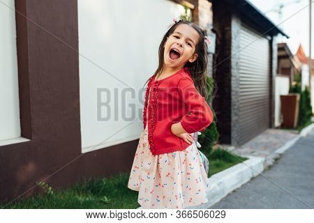Image Of Cute Little Girl Laughing During Coming Home After School Day Stading Near Her Home Outside
