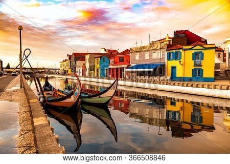 Aveiro, Portugal, Traditional Colorful Moliceiro Boats Docked In The Water Canal Among Historical Bu