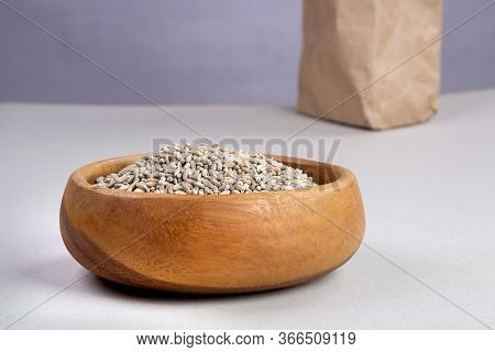 Unpeeled Raw Oats In A Wooden Plate On A Gray Background