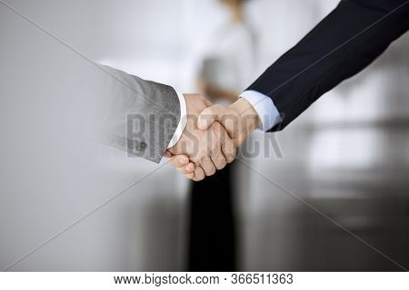 Business People In Office Suits Standing And Shaking Hands, Close-up. Business Communication Concept
