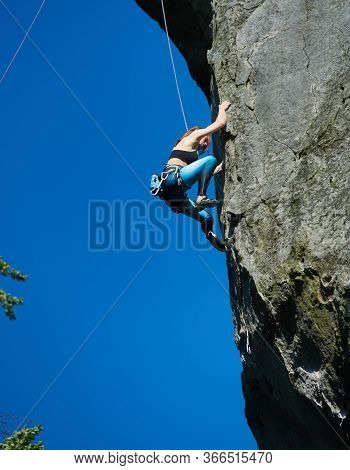 Lady Mountaineer In Sportswear Climbing Rock Under Blue Sky. Young Woman Climber Ascending High Moun