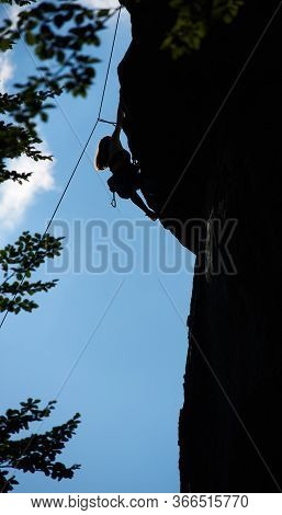 Silhouette Of Young Lady Climbing Extremely Vertical Rock Under Beautiful Blue Sky. Young Woman Alpi