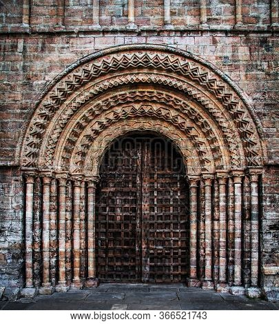 An Ornate And Grand Entrance To A Large Church With Heavy Wooden Door Surrounded By Ornate Stone Pil