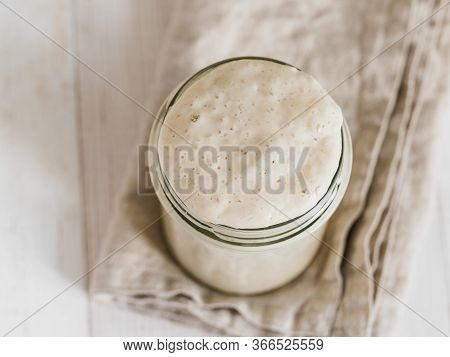 Wheat Sourdough Starter. Top View Of Glass Jar With Sourdough Starter On White Wooden Background. Co