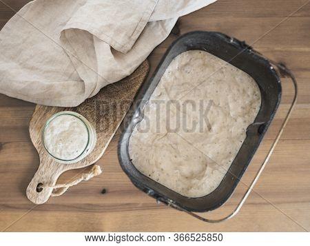 Wheat Sourdough Starter In Glass Jar And Sourdough In Bread Pan Of Bread Maker Machine. Homemade Bre