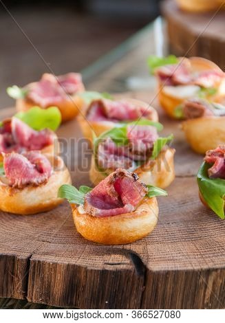Bite-sized, Mini Yorkshire Pudding With Rare Beef And Basil On A Wood Tray. Appetizer.