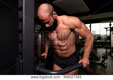 Muscular Fitness Bodybuilder Doing Heavy Weight Exercise For Triceps And Chest On Parallel Bars In T