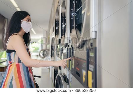 Beautiful Woman With Mask Doing Laundry At Laundromat Shop.