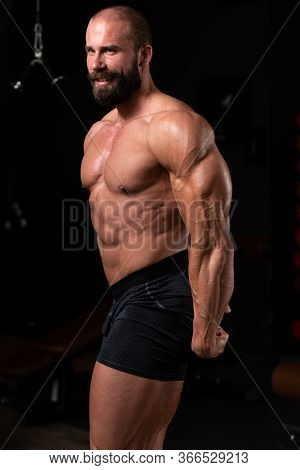 Muscular Man Flexing Muscles Side Triceps Pose