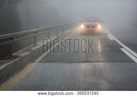 Fog On The Road In The Mountains.a Car Drives Through The Fog With Its Lights On. Insufficient Visib