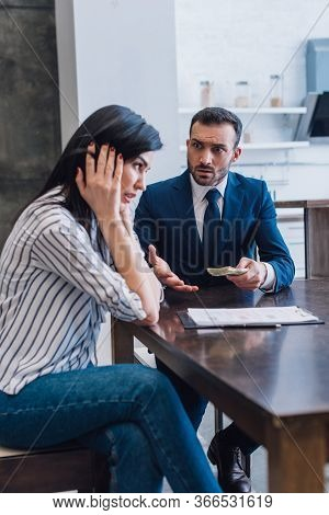 Tense Collector With Money Looking At Woman At Table In Room