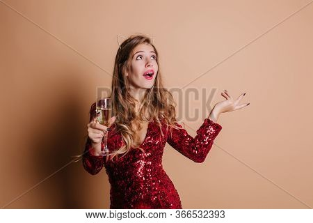 Emotional Woman With Glass Of Champagne Telling Something And Waving Hand. Sensual Girl In Red Spark