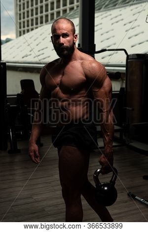 Young Man Exercising With Kettle Bell And Flexing Muscles - Muscular Athletic Bodybuilder Fitness Mo