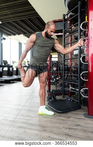 Young Fitness Man Stretches In A Gym