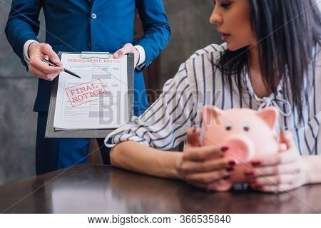 Cropped View Of Woman With Piggy Bank At Table Near Collector Pointing With Pen At Documents With Fi