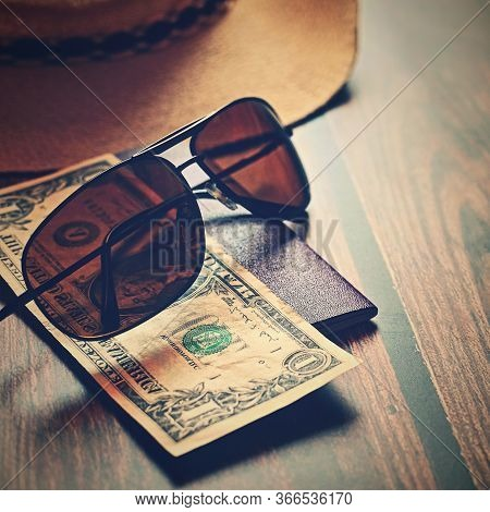 Items For Summer Vacation: A Camera, Passport,smartphone, Money, Hat, Sunglasses. Wooden Background,