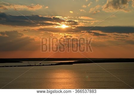 Pictured Is A Sunset In Orange-gold Tones Over The Estuary.