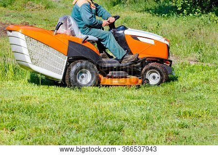A Service Worker Mows Grass On The Lawn With A Professional Lawn Mower On A Clear Sunny Day, Copy Sp