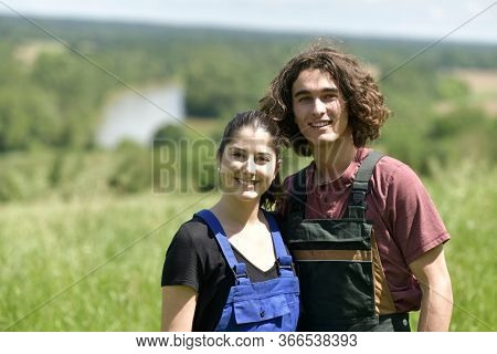 Young couple spending green vacation at the farm