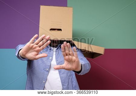 Weird, Scared Man With A Box On His Head Makes A Stop Gesture. Concept Of Fear Of Society And Shelte