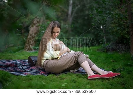 Young Mother Breast Feeding Her Baby On Nature Background. Breast-feeding. Motherhood And Care Conce