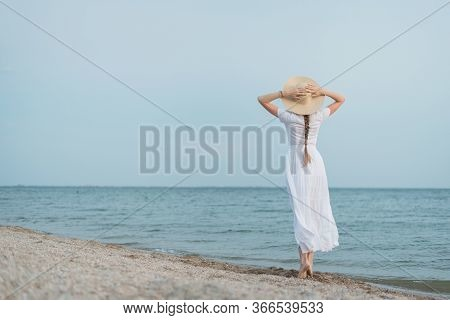 Delicate Young Woman In White Dress And Hat Walks On Sea Shore. Back View.