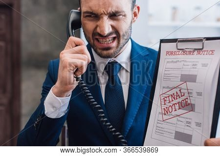 Angry Collector With Handset And Documents With Foreclosure And Final Notice Lettering In Room