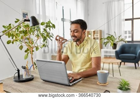 technology, remote job and lifestyle concept - happy indian man with laptop computer working and using voice command recorder on smartphone at home office