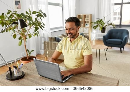 technology, remote job and lifestyle concept - happy indian man with laptop computer working at home office