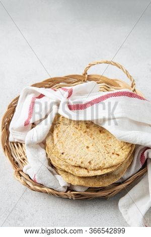Stack Of Mexican Corn Tortillas In A Wicker Tray Covered With Kitchen Towel