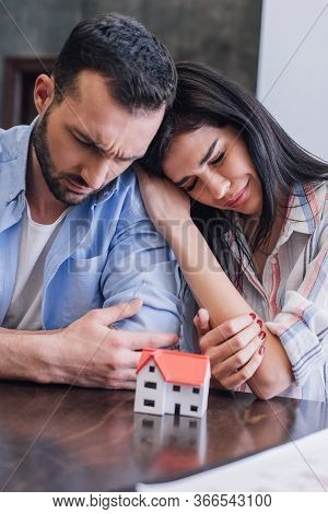 Woman Crying And Leaning To Tense Man Near House Model At Table