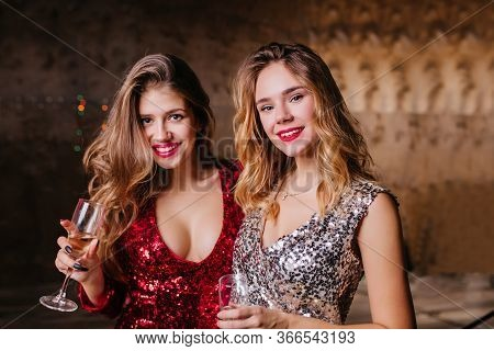 Close-up Portrait Of Interested Good-looking Ladies Standing On Dark Background With Wine. Adorable