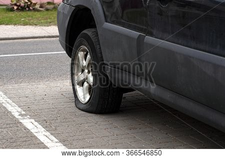 Car Wheel Flat Tire On The Road. Road Accident