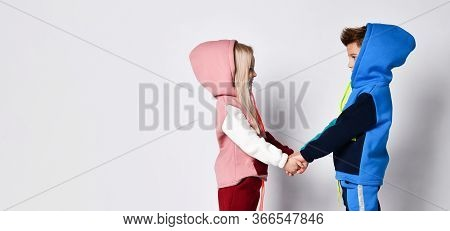 Little Kids, Brother And Sister, In Hoods, Colorful Tracksuits . They Holding Hands, Posing Sideways