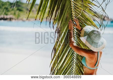 A Woman Wearing Sun Hat Near Coconut Palm Tree Leaves On A Tropical Anse Cocos Sandy Beach. La Digue