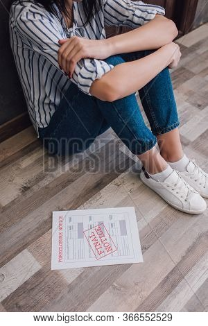 Cropped View Of Woman Sitting On Floor Near Document With Foreclosure And Final Notice Lettering In