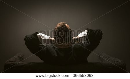 Businessman Pondering New Startup Project Sitting On A Sofa. Rear View Of Man In Black Suit Sitting