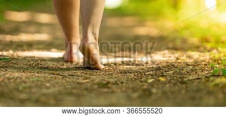 Bare Feet Of A Woman Walking Along A Trail In The Woods