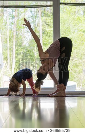 Young Mother And Her Toddler Daughter Practicing Yoga Together At Home In Living Room.