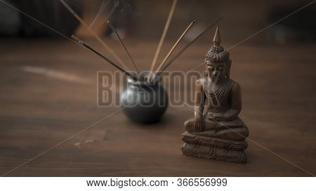 Workplace In Oriental Style With Incense Sticks And Buddha Statuette On A Wooden Table. Meditation C