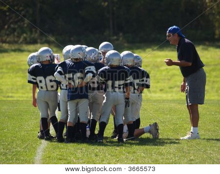 young american footbal team in a huddle on the field with the coach poster
