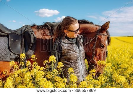 Young Woman Staying Near Brown Horse In Yellow Rape Or Oilseed Field With Blue Sky On Background At