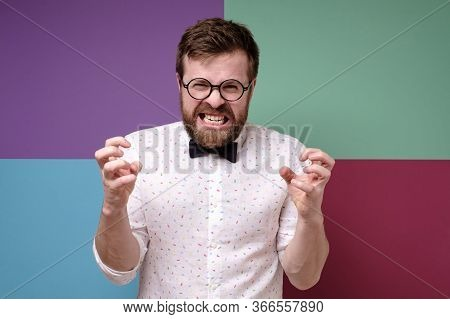 Irritation Man With Round Glasses, A Shirt And A Tie Furiously Clenches Hands And Grins Teeth.