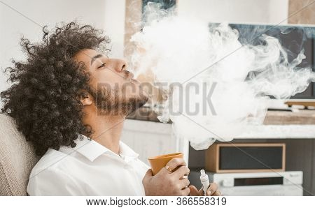 Young Man Smoking Of Electronic Cigarette At Home. Smoker Exhales Big Cloud Of Smoke, Prifile View O