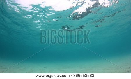 Sandy bottom and blue water in sea. Underwater background photo