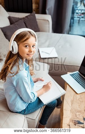Happy Kid In Wireless Headphones Writing In Notebook Near Laptop With Blank Screen While E-learning