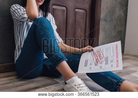 Cropped View Of Woman Holding Document With Foreclosure And Final Notice Lettering On Floor In Room